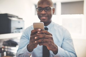 Smiling African businessman using a cellphone in an office