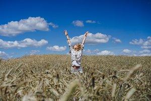 girl is having fun in wheat field