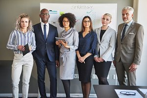 Focused team of diverse business strategists standing in an office
