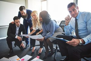Corporate professionals discussing paperwork together in an office