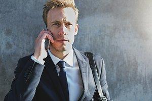 Businessman using phone and looking at camera