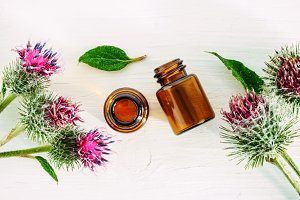 burdock oil in small glass bottle, top view, copyspace