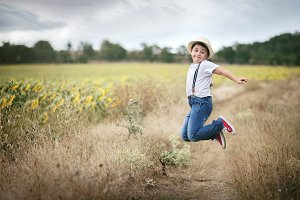 Smiling boy jumping in the field