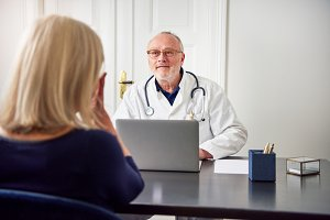 Medical consultant sitting and listening to patient at computer