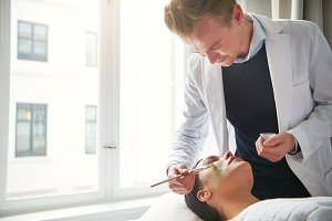 Cosmetologist applying mask on female face at cosmetology procedure