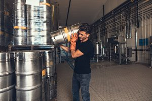 Brewer with keg at brewery factory