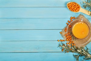 Sea buckthorn juice or tea with berries on a blue wooden background with copy space for your text. Top view