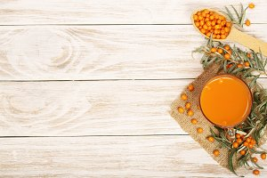 Sea buckthorn juice or tea with berries on a white wooden background with copy space for your text. Top view