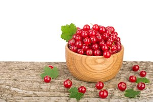 Red currant berries in wooden bowl on wooden table with white background