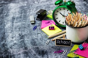 School stationery, pencil, pen, note, alarm clock on grunge chalkboard
