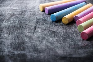 Pieces of school chalk on old black chalkboard