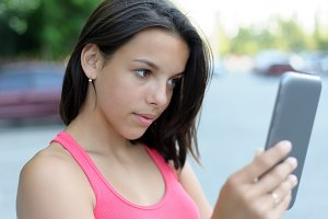 Girl using tablet PC outdoor
