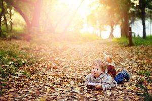 Happy kid boy in autumn park