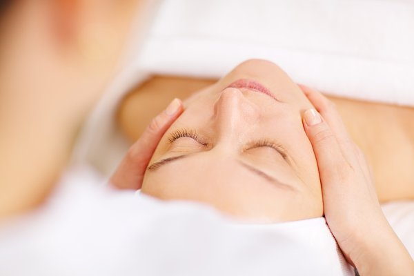 Woman under facial massage in spa