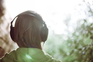 Woman in headphones against Sun