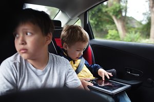 Two boys traveling on the back seat