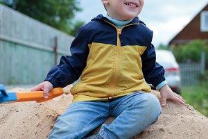 Happy little boy sitting on sand