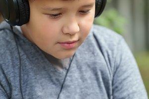 Teenager in headphones using pad