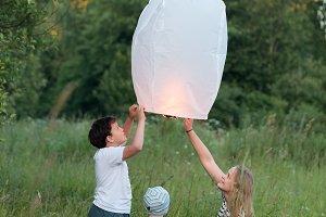 Family of three flying paper lantern