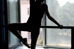 Ballet dancer exercising barre