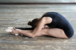 Ballet dancer stretching out sitting