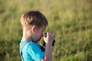 Little boy with camera outdoor