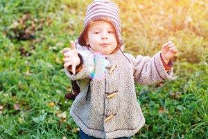 Happy kid boy in park walking