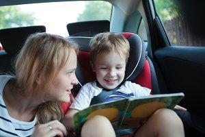 Boy holding book sitting in a car