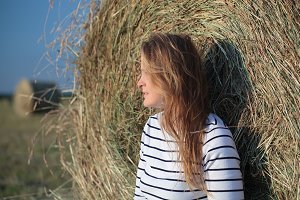 Young woman by the hay roll