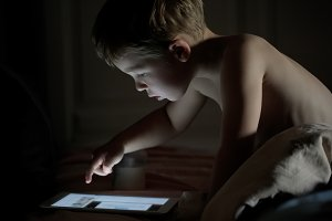 Little boy using tablet PC at night