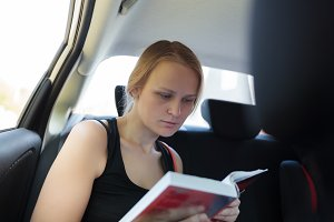 Woman reading a book in the car