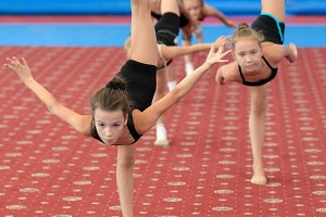 Young female gymnasts doing vertical