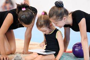 Three gymnast girls with tablet