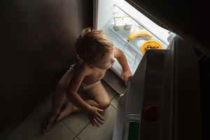Little boy sitting near open fridge