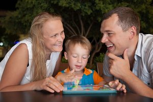 Happy family with tablet PC outdoor