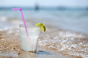 Glass of lemonade or water on beach