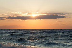 Rough sea and sunset over it