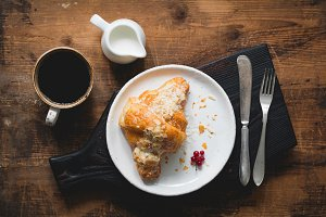 Croissant, coffee and cream on dark cutting board