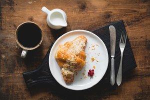Croissant, coffee and cream on dark cutting board