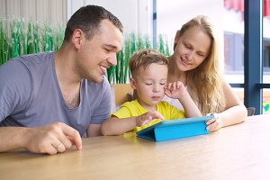 Happy family of three with tablet