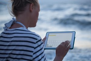 Woman typing on tablet PC by sea