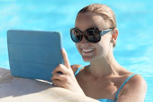 Young woman in a pool using tablet c