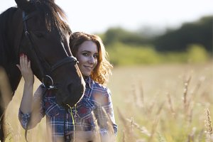 Woman and horse in the meadow at summer evening