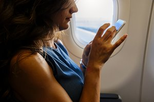 Woman using mobile into the plane.
