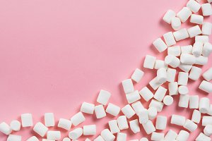 Marshmallows on pink background with copyspace
