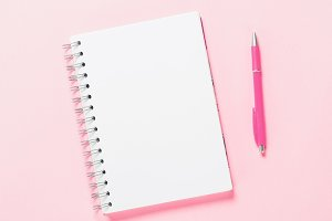 Top view of blank note with pen on pink background