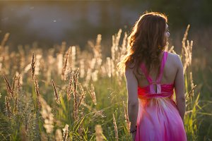Attractive young woman walking on meadow at sunset - rear view