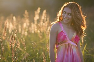 Portrait of a attractive woman posing in summer meadow at sunset