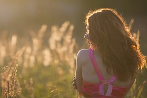 Attractive young woman in meadow at sunset - rear view