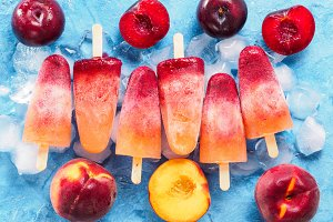 top view of plum and peach popsicle on blue background